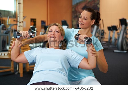 Woman doing weight training with female fitness coach - stock photo