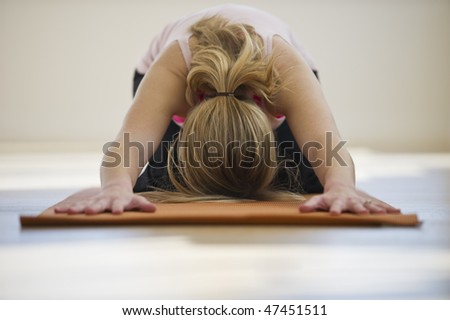 woman doing yoga alone on mat in studio