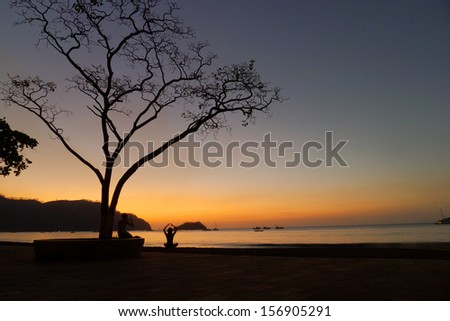 Woman doing yoga and meditation at sunset in Costa Rica