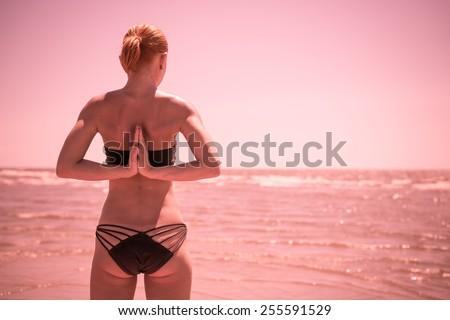 Woman doing yoga asana reverse namaste at the beach - stock photo