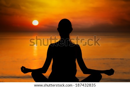 Woman doing Yoga at sunset  - stock photo