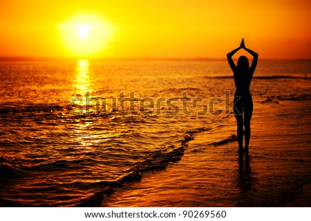 Woman doing yoga at sunset on the seashore - stock photo
