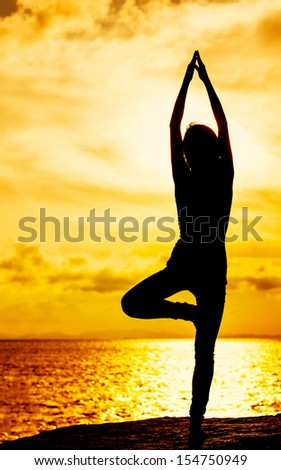 Woman doing yoga during sunset - stock photo