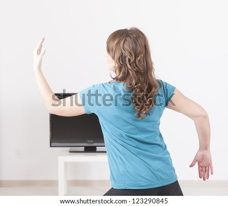 Woman doing yoga exercise at home using on screen TV instructions - stock photo