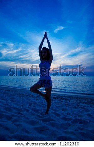 woman doing yoga exercise at the sunset beach
