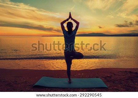 Woman doing yoga exercise in pose of tree on beach near the sea at sunset in summer, rear view