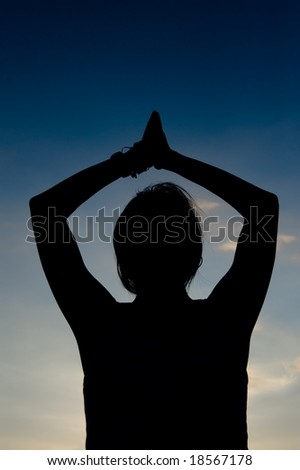 woman doing yoga exercise in silhouette - stock photo