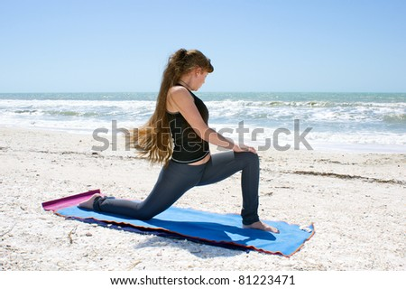 woman doing yoga exercise woman doing yoga exercise  Salamba Kapotasana or Supported Pigeon Pose on an empty beach at the gulf of mexico in bonita springs floridawith long hair blowing in wind - stock photo