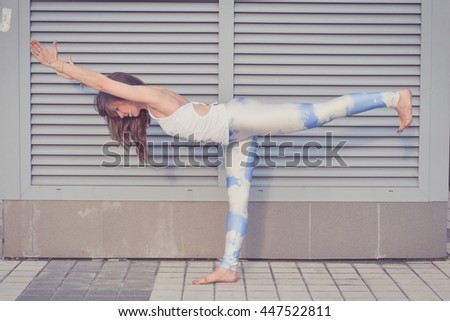 Woman doing yoga exercises outdoors in the city.  Beautiful brunette fit young woman wearing sportswear practicing yoga urban style. Working out, fitness, sport, training and lifestyle concept - stock photo