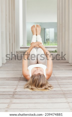 woman doing yoga in a spacious interior - stock photo