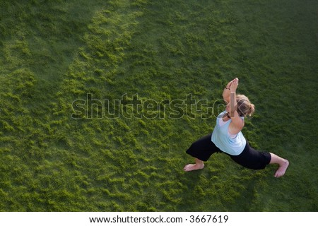 Woman doing yoga in the grass. Shot from above. - stock photo