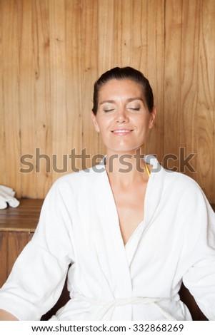 Woman doing yoga in the sauna - stock photo