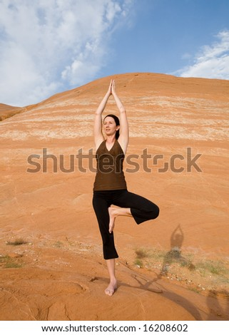 Woman doing yoga in the wilderness at sunset against a beautiful wilderness backdrop