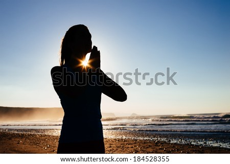 Woman doing yoga meditation and relaxing breathing exercises at beach. - stock photo