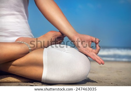 Woman doing yoga meditation in white costume on the beach in Goa, India - stock photo