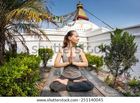 Woman doing yoga meditation near Bodnath stupa, Kathmandu, Nepal - stock photo
