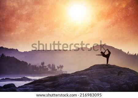 Woman doing Yoga natarajasana dancer pose on the rocks at sunset at Om beach, Gokarna, India - stock photo