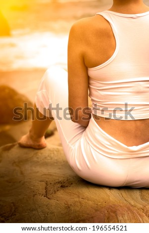 Woman doing yoga on a beach - stock photo