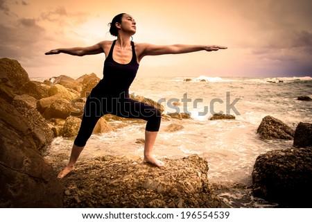 Woman doing yoga on a beach - stock photo