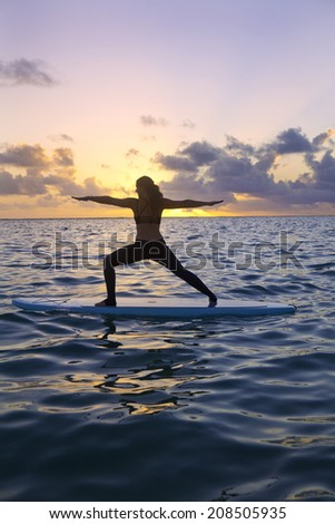 woman doing yoga on a stand-up paddle board in the ocean at sunrise