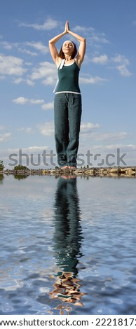 woman doing yoga on a stone above  water