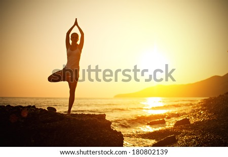 woman doing yoga on the beach by the sea at sunset - stock photo