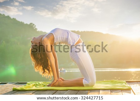 Woman doing yoga on the lake - relaxing in nature - stock photo