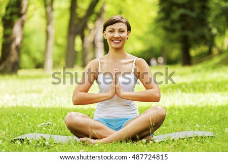Woman doing yoga on the meadow with smile.