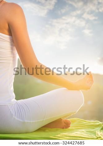 Woman doing yoga on the shore - half figure sitting - stock photo