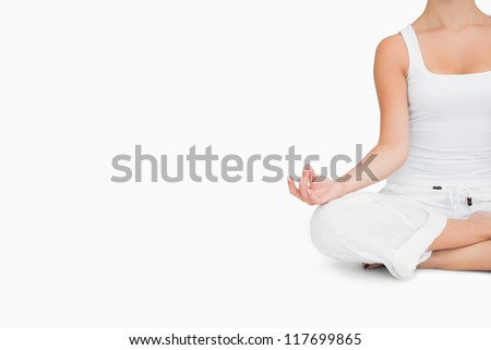 Woman doing yoga pose while sitting cross legged - stock photo