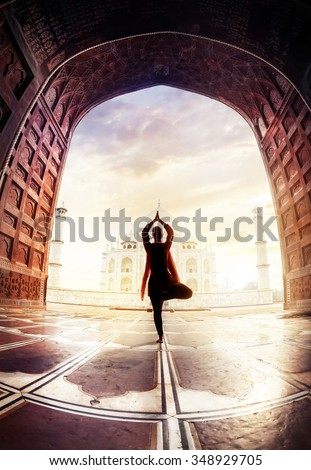 Woman doing yoga tree pose with red scarf in silhouette near Taj Mahal in Agra, Uttar Pradesh, India