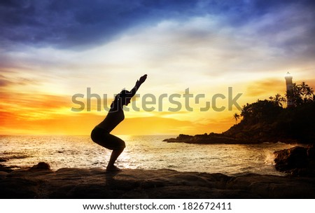Woman doing Yoga Utkatasana pose in silhouette on the stones near lighthouse at sunset sky in Kovalam, Kerala, India - stock photo