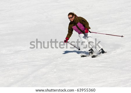 Woman downhill skiing on wide piste - stock photo