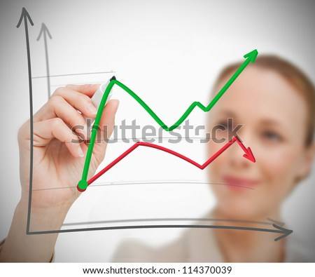 Woman drawing a graph with pen on grey background - stock photo