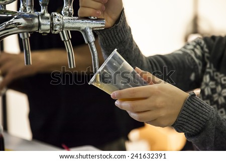 Woman drawing beer from tap in an inclined plastic cup  - stock photo