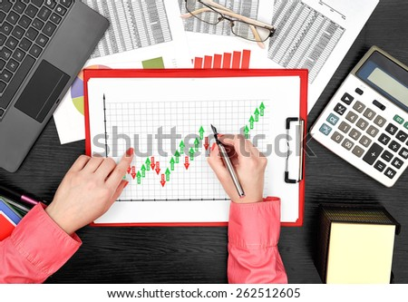 woman drawing forex chart on clipboard sitting in office - stock photo