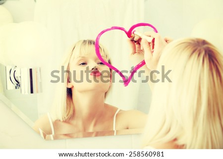 Woman drawing heart by lipstick on a mirror. - stock photo