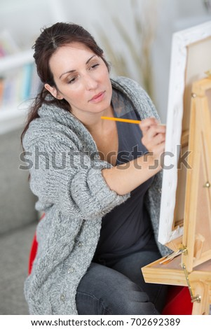 woman drawing pencil portrait on floor in workshop