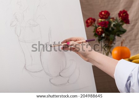 Woman draws a still life on a white canvas - stock photo