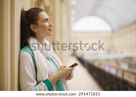 woman dreaming with smartphone in her hands - stock photo