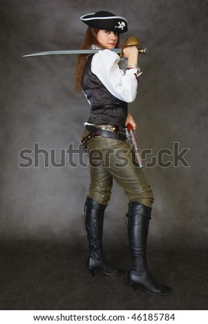 Woman dressed as a pirate standing on a black background with a sword