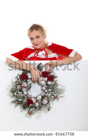 Woman dressed as Mrs. Claus and holding a wreath
