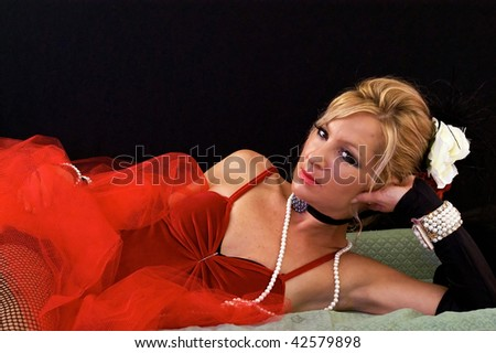 Woman dressed as old time saloon girl or prostitute laying down could also be used as mrs santa claus or a sexy elf. Shot under red and blue strobes. - stock photo