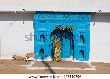 Woman dressed in a green sari leaves the house, built in the traditional style of North India - stock photo