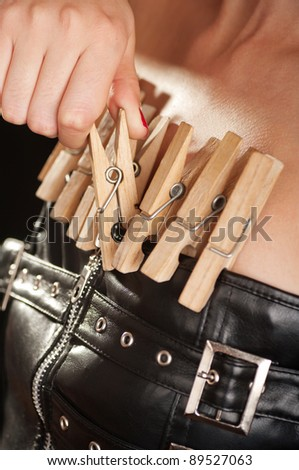 Woman dressed in a leather corsette with wooden clothespins attached to it