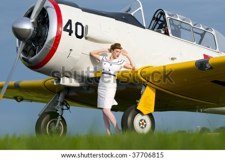 woman dressed in a retro navy attire standing next to a vintage aircraft - stock photo