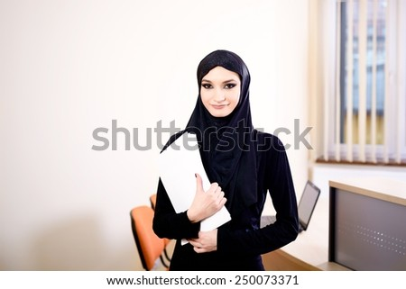 Woman dressed in black and wearing the hijab while working in the office.  In her hand she holds the documents - stock photo