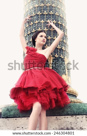 "Woman dressed in red ballerina dress, high up on fence near a pillar from the famous public square "" Place de la Concorde"", Paris. - stock photo"