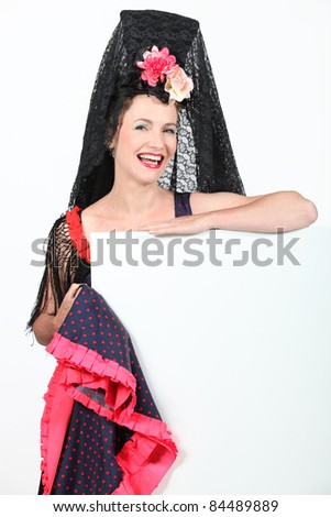 Woman dressed in Spanish outfit holding blank message board - stock photo