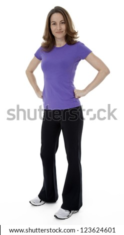 Woman dressed in sportswear with hands on hips, standing on white background. - stock photo